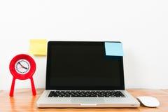 膝上型计算机和红色时钟在黑木桌上 免版税库存照片