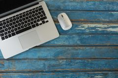 膝上型计算机和老鼠在木桌上 库存照片