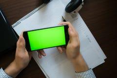 膝上型计算机和耳机智能手机有绿色屏幕的关键chrom的 免版税库存照片
