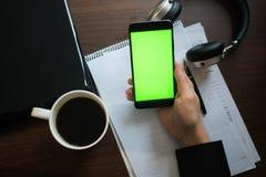 膝上型计算机和耳机智能手机有绿色屏幕的关键chrom的 库存图片