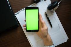 膝上型计算机和耳机智能手机有绿色屏幕的关键chrom的 库存照片