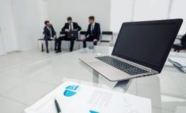 膝上型计算机和财政日程表在桌上的办公室 图库摄影