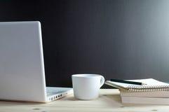 膝上型计算机咖啡和书在木书桌上 免版税库存照片