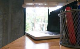 膝上型计算机在一张木桌上站立 库存图片