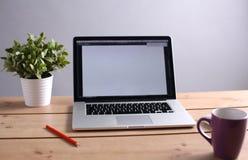 膝上型计算机在一张木桌上站立 免版税库存图片