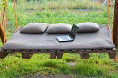 膝上型计算机在吊床说谎户外,自由空间 免版税库存图片
