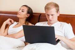 膝上型计算机在夫妇的床上 库存图片