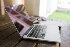 膝上型计算机在木桌上的笔记本计算机 免版税库存照片