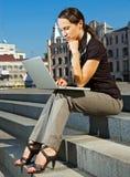 膝上型计算机坐的台阶妇女 免版税图库摄影