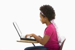 膝上型计算机女小学生 图库摄影