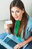 膝上型计算机妇女 抽象蓝色看板卡赊帐照片 在长沙发的Shpping 免版税库存照片