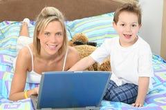 膝上型计算机妈妈儿子 库存图片