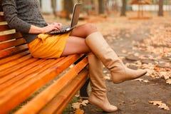 膝上型计算机室外使用妇女年轻人 免版税库存照片