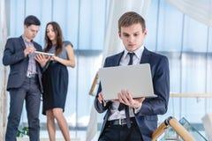 膝上型计算机工作者 站立在的年轻和成功的商人 免版税库存照片