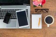 膝上型计算机手机和片剂有笔记本的在书桌上 图库摄影