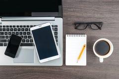 膝上型计算机手机和片剂有笔记本的在书桌上 库存照片