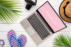 膝上型计算机显示的嘲笑在白色木桌上的夏天休假假期背景概念的 舱内甲板笔记本被放置的顶视图  免版税库存图片