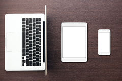 膝上型计算机片剂和电话在桌面看法 免版税库存图片