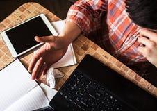 膝上型计算机片剂和笔记本有铅笔的在桌上与一个人 免版税库存图片