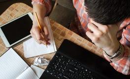 膝上型计算机片剂和笔记本有铅笔的在桌上与一个人 免版税库存照片