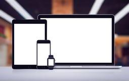 膝上型计算机片剂智能手机和smartwatch大模型与白色屏幕在书桌上在办公室空间 免版税库存照片