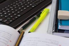 膝上型计算机片剂键盘,与算术惯例的被打开的课本,铅笔,堆学校笔记本,在白色桌面上的轮廓色_ 免版税库存照片