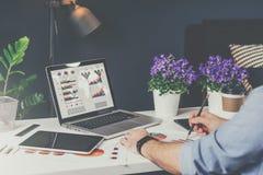 膝上型计算机特写镜头有图表、图和图的在屏幕上 在桌上是数字式片剂,纸图表,房子植物 库存照片