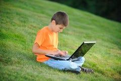 膝上型计算机男小学生工作 库存照片