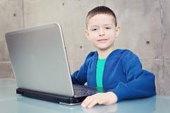 膝上型计算机男小学生 库存照片