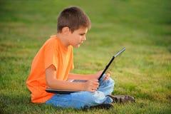 膝上型计算机男小学生 库存图片