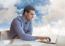 膝上型计算机的人在多云天空 免版税库存图片