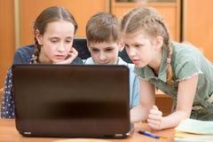 膝上型计算机的愉快的孩子在教室 免版税库存照片