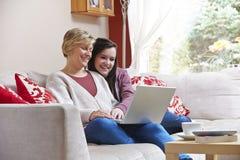 膝上型计算机的母亲和女儿 免版税库存照片