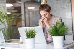 膝上型计算机的疲倦的,被注重的女实业家在办公室 免版税库存照片