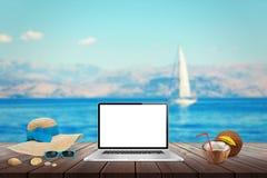 膝上型计算机被隔绝的显示在木桌上的大模型的 海、游艇和蓝天在背景中 库存照片