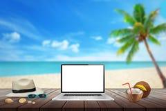 膝上型计算机被隔绝的显示在木桌上的大模型的 海滩、海、棕榈和蓝天在背景中 库存图片