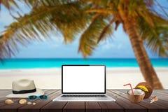膝上型计算机被隔绝的显示在木桌上的大模型的 海滩、海、棕榈和蓝天在背景中 库存照片