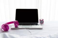 膝上型计算机运转在闹钟附近的和桃红色耳机在晴天早晨假日听在白色床上的音乐 免版税库存图片