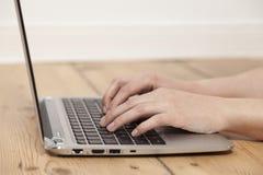 膝上型计算机键入的妇女 库存照片