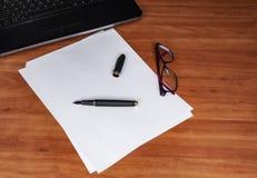 膝上型计算机键盘、白皮书、墨水笔和玻璃在一张木桌上 您的拷贝文本的空的空间 免版税库存照片