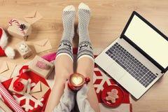 膝上型计算机顶视图在女孩` s的递坐与咖啡的一个木地板、圣诞节装饰、礼物和包装纸 免版税图库摄影