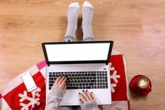 膝上型计算机顶视图在女孩` s的递坐与咖啡的一个木地板、圣诞节装饰、礼物和包装纸 免版税库存照片