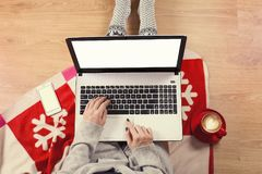 膝上型计算机顶视图在女孩` s的递坐与咖啡的一个木地板、圣诞节装饰、礼物和包装纸 免版税库存图片