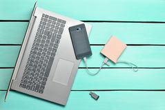 膝上型计算机,智能手机,力量银行, USB在一张蓝色木桌上的闪光驱动 现代数字式设备和小配件 顶视图 免版税库存照片