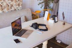 膝上型计算机,电话,在一个现代桌面上的照相机 库存照片