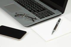 膝上型计算机,电话,笔记薄,笔,玻璃 库存图片