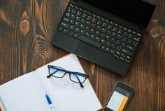 膝上型计算机,笔记本,电话,笔在地板放置 库存照片