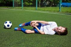 膝盖伤害在男孩橄榄球的 图库摄影
