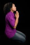 膝盖祈祷的妇女 免版税库存照片