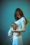 膝部的图象逗人喜爱的小女孩年轻母亲 妈咪 免版税库存照片